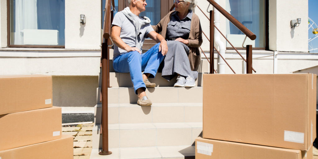 Portrait of happy senior couple sitting on porch of new house with cardboard boxes in foreground, copy space
